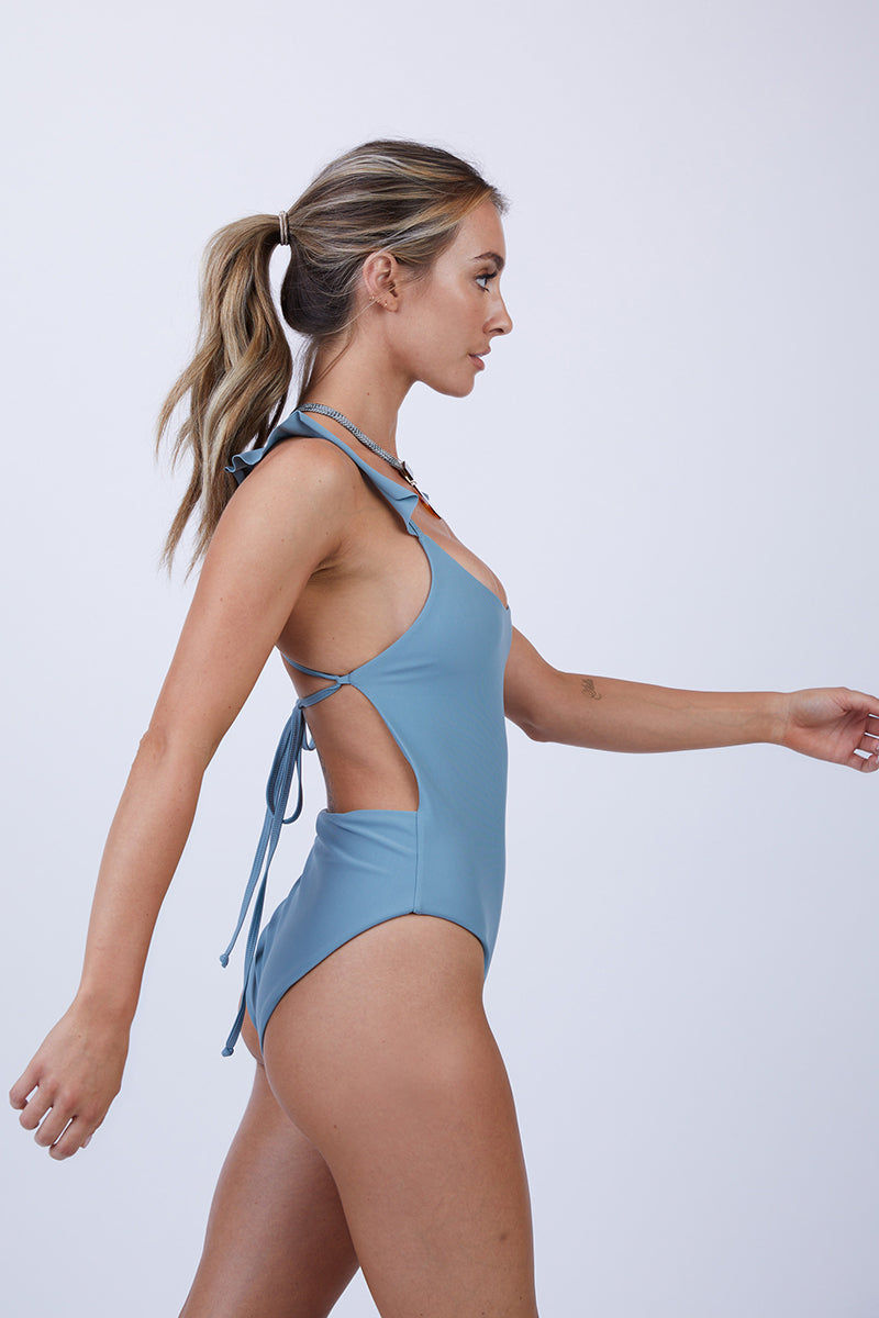 GILLIA Lillian Ruffle One Piece Swimsuit - Steel One Piece | Steel| GILLIA Lilian Ruffle One Piece Swimsuit - Steel Scoop Neckline  Ruffle Shoulder Detail  Adjustable Back Ties High Cut Leg  Moderate Coverage  80% Nylon / 20% Spandex Made in Indonesia Side View