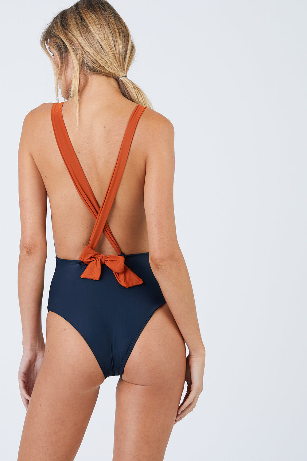 HAIGHT Marina Plunge One Piece Swimsuit - Rust & Black One Piece | Rust & Black| Haight Marina Plunge One Piece Swimsuit - Rust & Black Features: Deep V-neck Adjustable self-fastening crossover back straps Mid cut leg Moderate coverage Ties at back Crisscross back detail Bow knot low at the back Front View