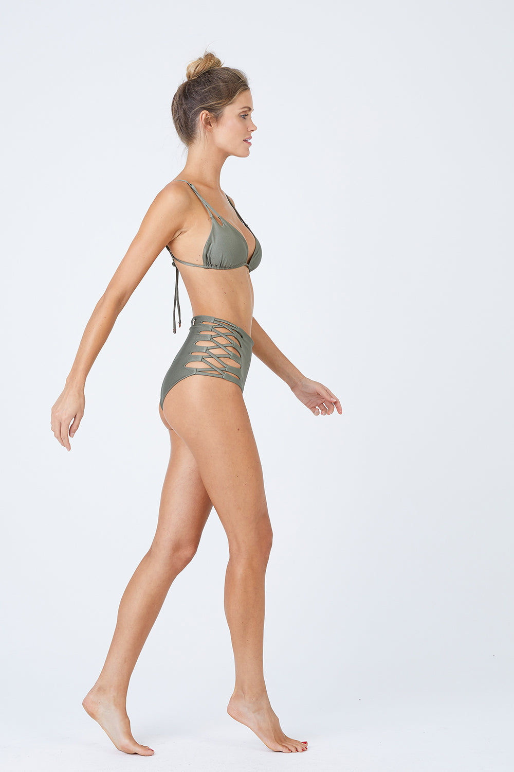 MALAI Lace Up High Waist Bikini Bottom - Sparkly Green Bikini Bottom | Sparkly Green| Malai Malai Lace Up High Waist Bikini Bottom - Sparkly Green Retro style high-waisted bikini bottom in shiny autumn green color. Intricate corset-inspired criss-cross strap detail at sides adds a sexy touch Side View