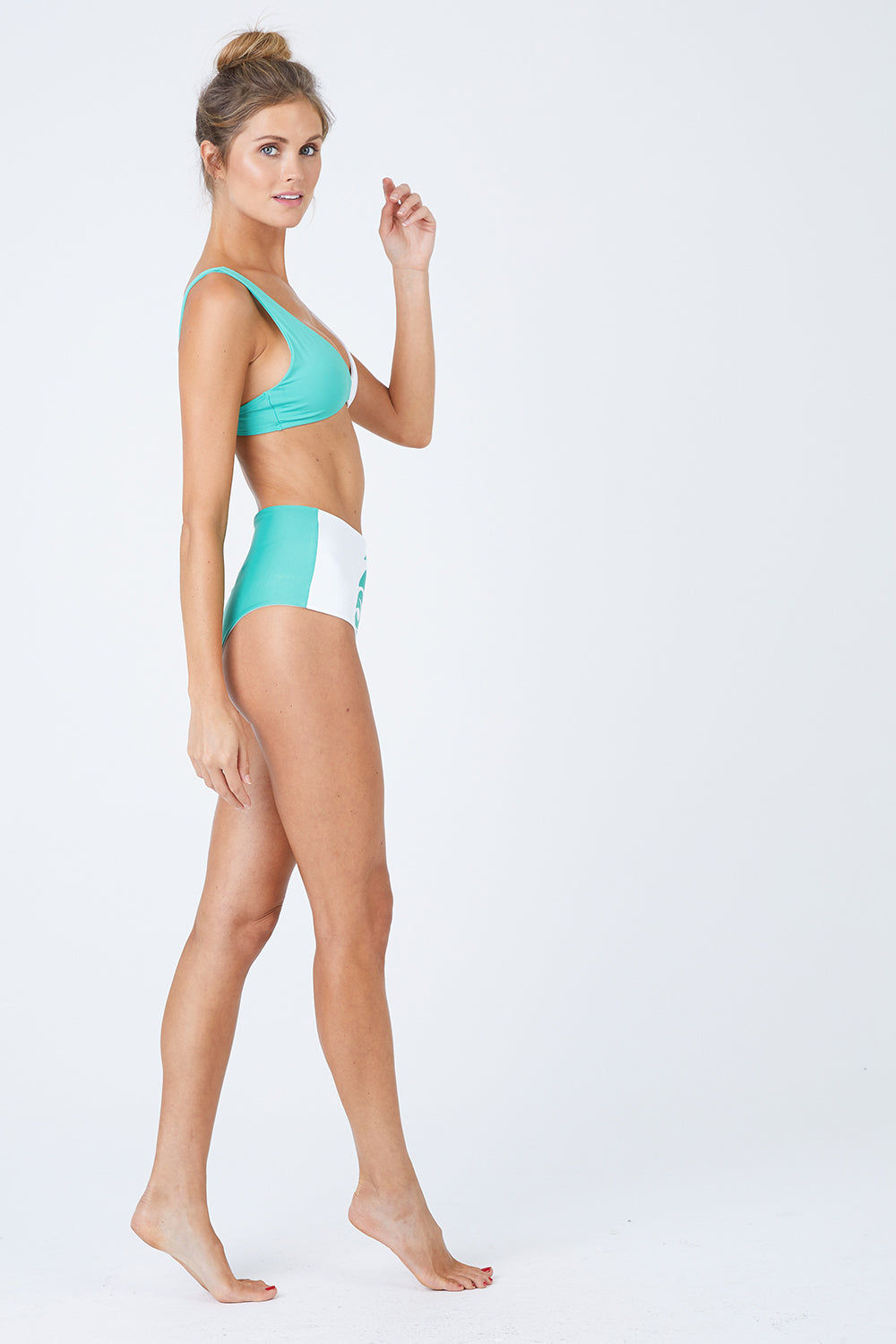 L SPACE Ozzie Color Block Bikini Top - Spearmint/White Bikini Top |  Spearmint/White| L Space Ozzie Color Block Bikini Top - Spearmint/White. Color block design Removable pads S-hook bra closure with 3 loops for adjustability Size XS-L 80% nylon, 20% spandex Made in the USA Like all delicates, shape, color and fit are best preserved if hand washed in cold water. Lay flat to dry. Front View