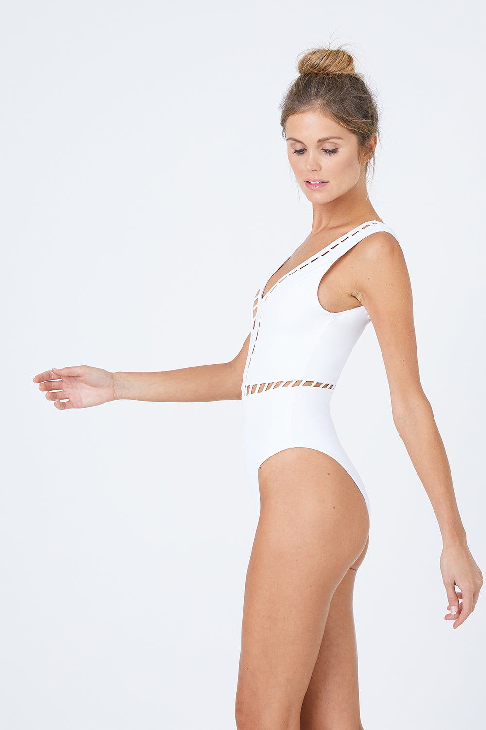 OYE SWIMWEAR Ela Plunge Cut Out High Cut One Piece Swimsuit - White One Piece | White| Oye Swimwear Ela Plunge Cut Out High Cut One Piece Swimsuit - White White deep v-neck one piece swimsuit with cut-out pattern. Wide strap, sleeveless pull-over design features a deep v-shaped back Geometric cut-out high cut leg moderate coverage Side View
