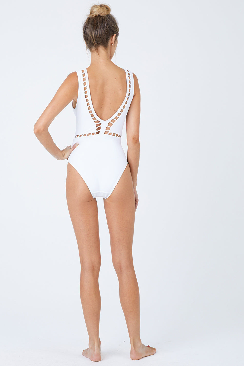 OYE SWIMWEAR Ela Plunge Cut Out High Cut One Piece Swimsuit - White One Piece | White| Oye Swimwear Ela Plunge Cut Out High Cut One Piece Swimsuit - White White deep v-neck one piece swimsuit with cut-out pattern. Wide strap, sleeveless pull-over design features a deep v-shaped back Geometric cut-out high cut leg moderate coverage Back View
