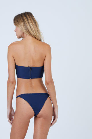 ONIA Rochelle Thin Side Strap Bikini Bottom - Deep Navy Bikini Bottom | Deep Navy| Onia Rochelle Thin Side Strap Bikini Bottom - Deep Navy Features:   Low Rise  Fixed Thin Side Straps  Cheeky Coverage  Ribbed Fabric  Back View