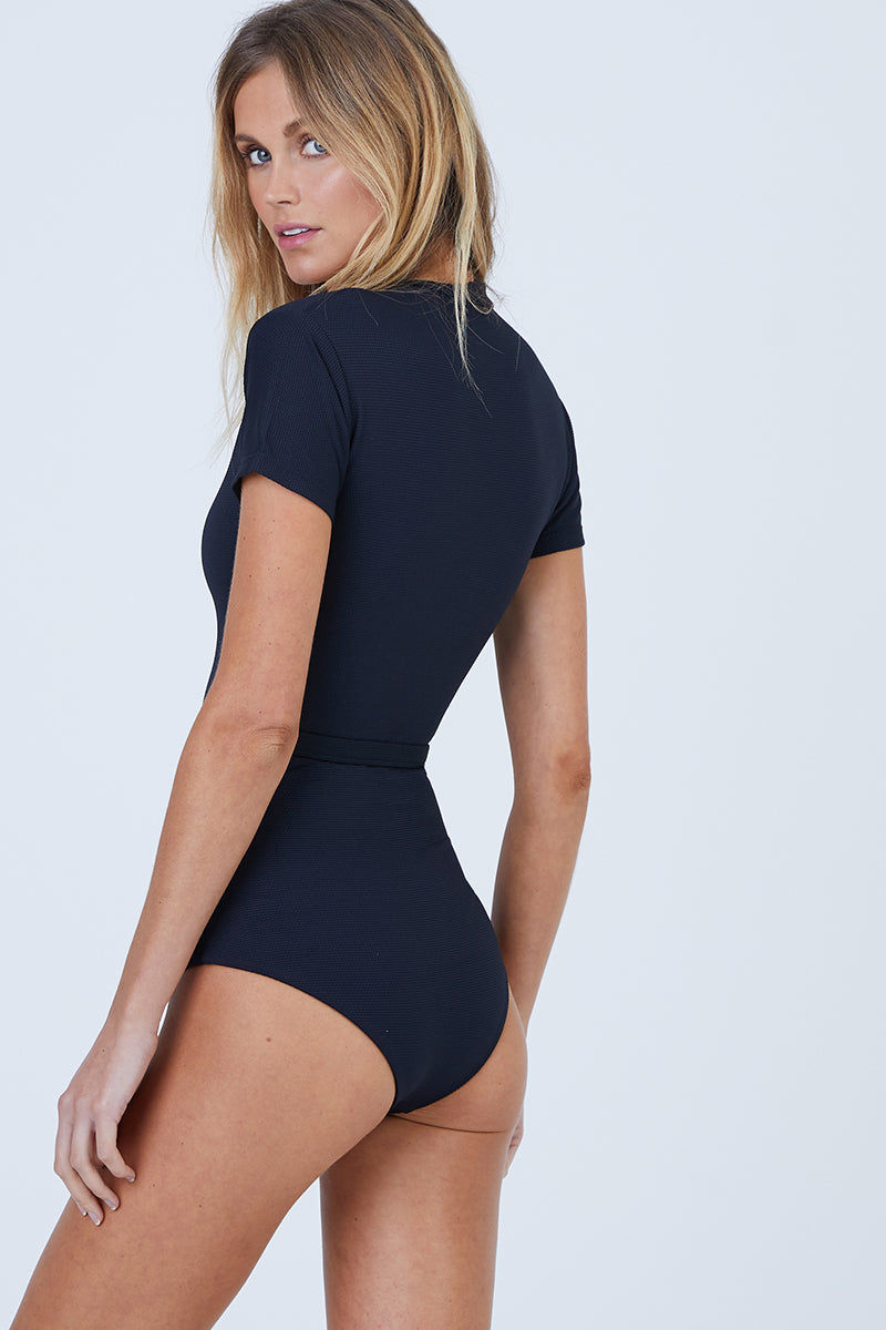 AILA BLUE Pierce Short Sleeves One Piece Swimsuit - Black Waffle One Piece   Black Waffle  Aila Blue Pierce Short Sleeves One Piece Swimsuit - Black Waffle High neck Short sleeves Belted surf suit Zipper front closure Cheeky coverage Back View