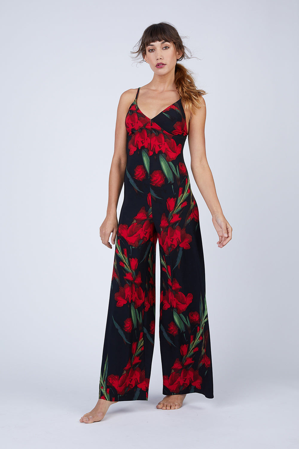 NORMA KAMALI Slip Jumpsuit - Blooming Roses Print Jumpsuit | Blooming Roses Print| Norma Kamali Slip Jumpsuit - Blooming Roses Print  Flowy stretch jersey jumpsuit in red and black floral print. Thin slip straps and simple tank neckline frame the minimalistic cut. Long, wide-leg trouser-style pant lengthens your frame in an easy breezy look. Front View