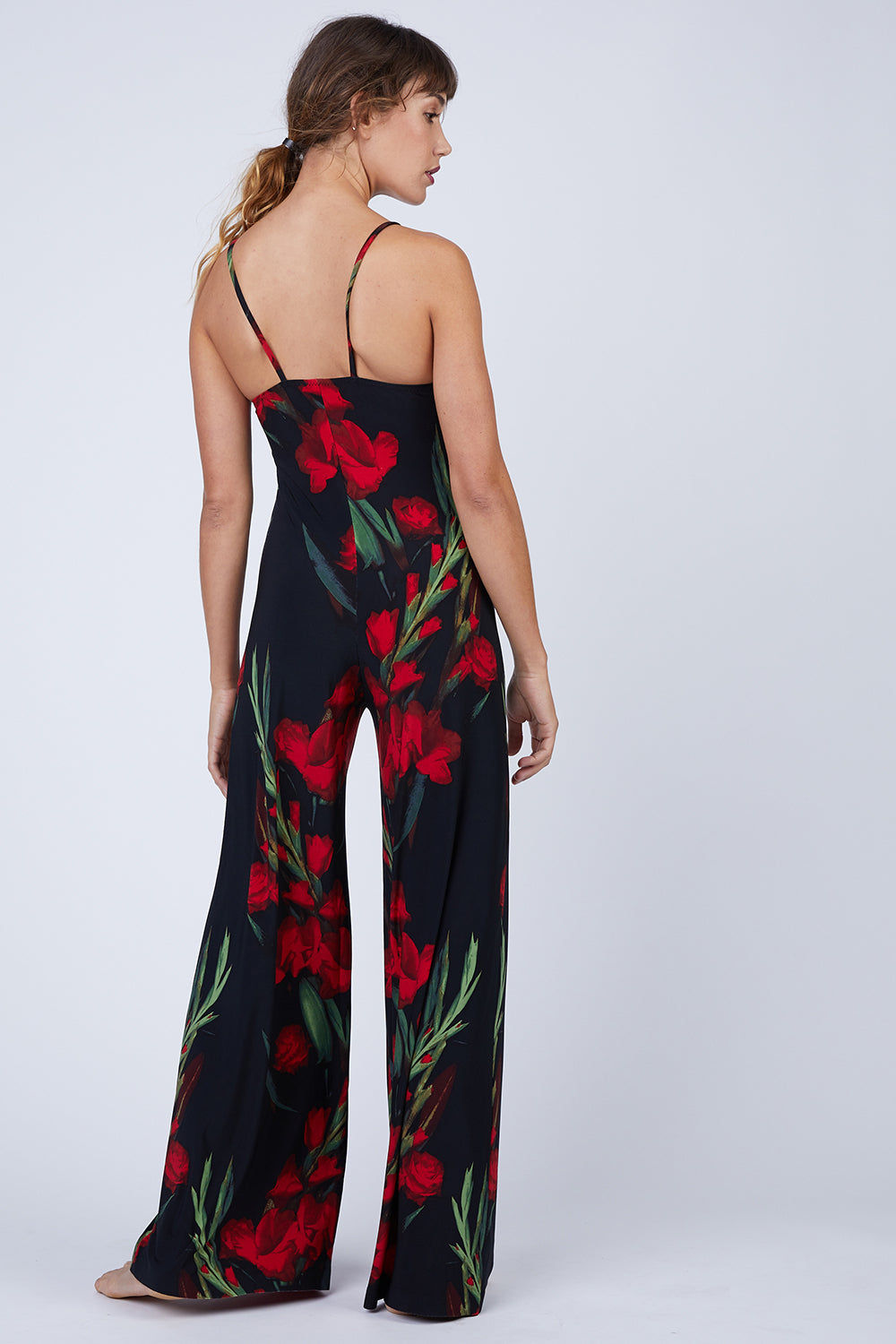 NORMA KAMALI Slip Jumpsuit - Blooming Roses Print Jumpsuit | Blooming Roses Print| Norma Kamali Slip Jumpsuit - Blooming Roses Print  Flowy stretch jersey jumpsuit in red and black floral print. Thin slip straps and simple tank neckline frame the minimalistic cut. Long, wide-leg trouser-style pant lengthens your frame in an easy breezy look. Back View