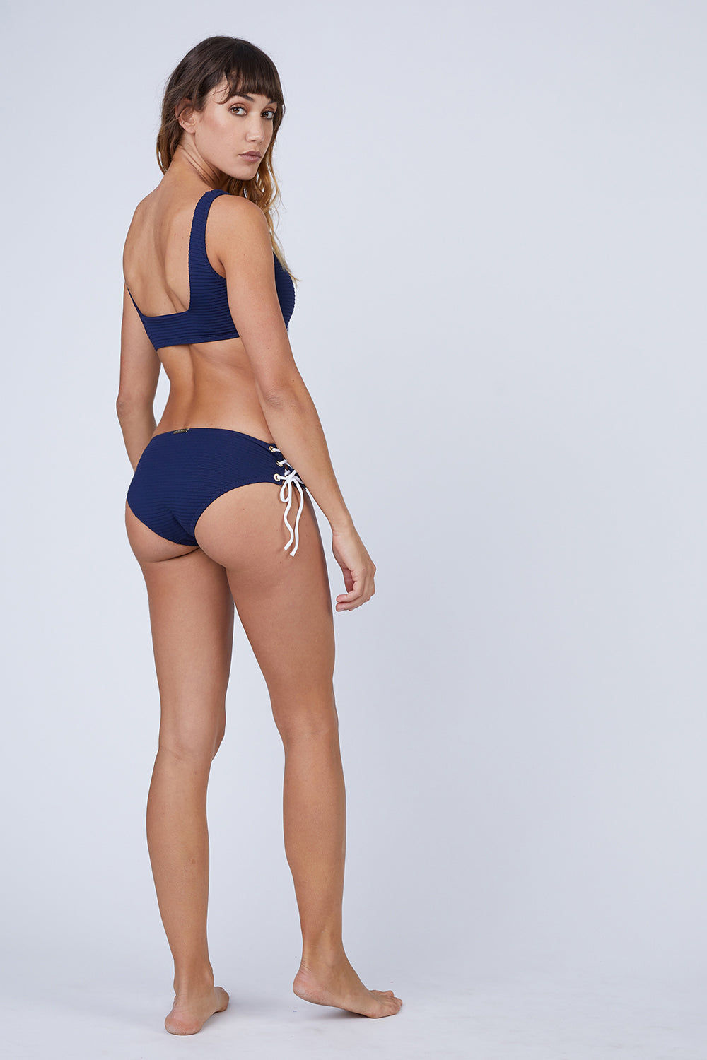 HEIDI KLEIN Ribbed Lace Up Mid Rise Bikini Bottom - Navy Blue Bikini Bottom | Navy Blue| Heidi Klein Ribbed Lace Up Mid Rise Bikini Bottom - Navy Blue. Features:  This style is cut to be High Rise and Mid Coverage. The waist and legs are elasticated for a secure, comfortable fit. Fully lined in soft lining for ultimate comfort. This high waisted style is cut with split side seams, fastened with decorative lacing. Back View