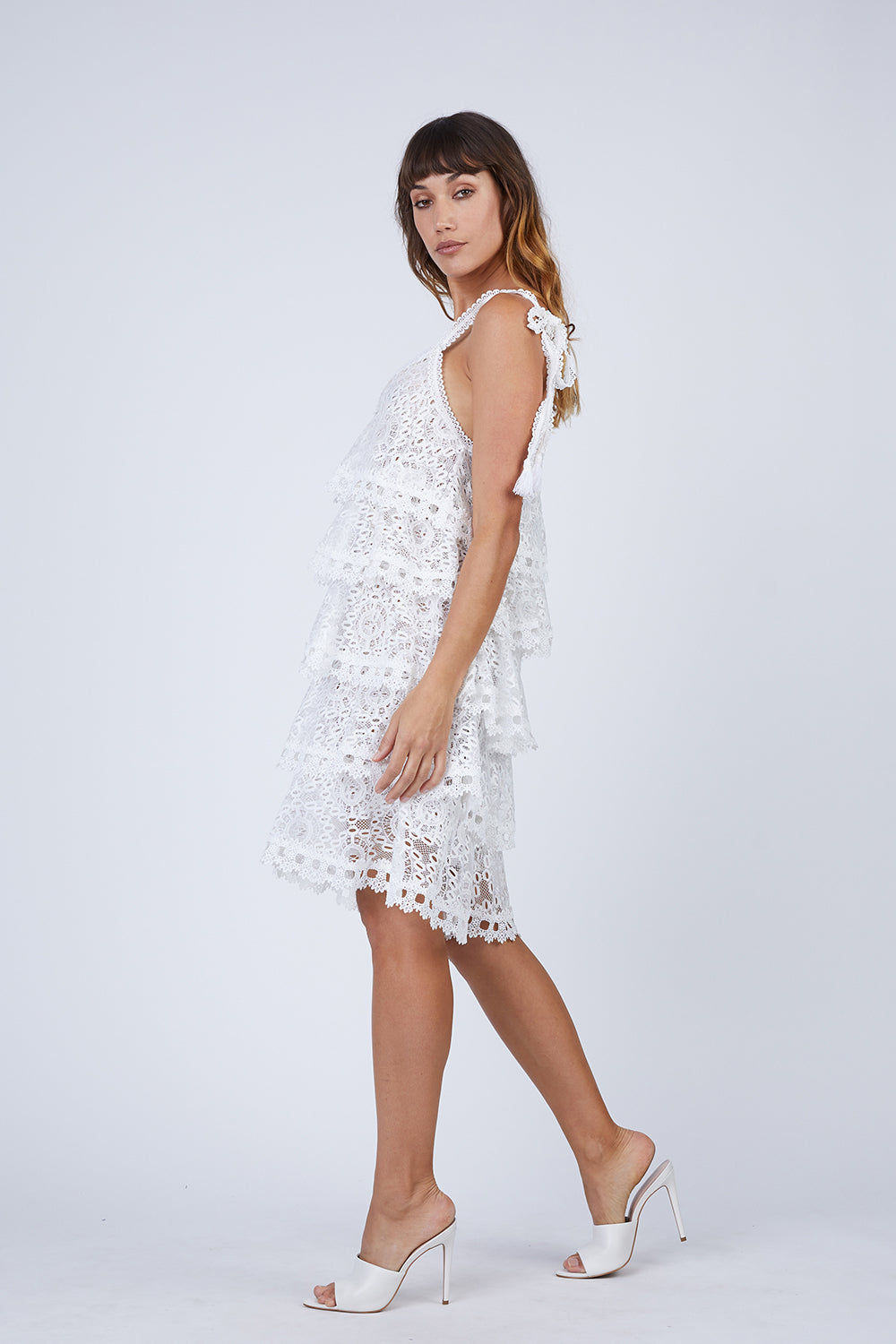 WAIMARI Audrey Tiered Ruffle Lace Sundress - Ivory White Dress | Ivory White| Waimari Audrey Tiered Ruffle Lace Sundress - Ivory White Lace dress V neckline  Ruffle tiers Shoulder ties with tassel ends  Side View