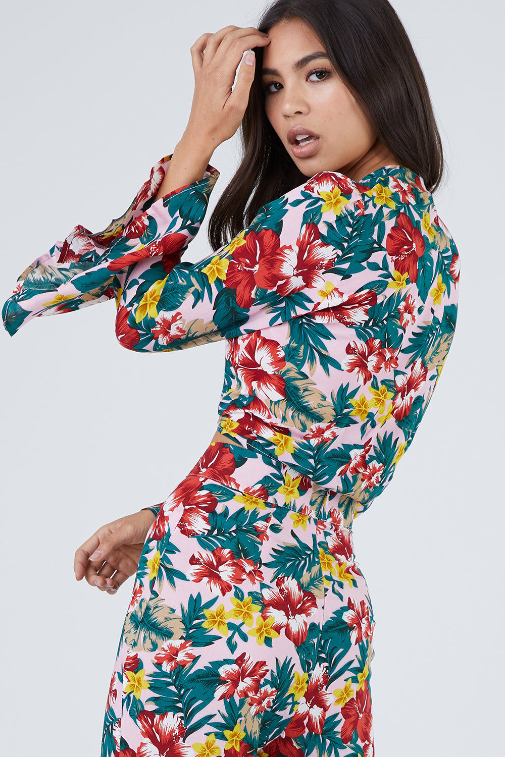 XIX PALMS Hana Bell Sleeves Front Knot Crop Top - Vibrant Floral Print Top | Vibrant Floral Print | XIX Palms Hana Bell Sleeves Front Knot Crop Top - Vibrant Floral Print Retro long bell sleeve V-neck front knot top in a vibrant tropical floral print. The seductive deep V-neckline pairs perfectly with pendant or lariat necklaces while showing off your décolletage. Adjustable front knot tie Back View