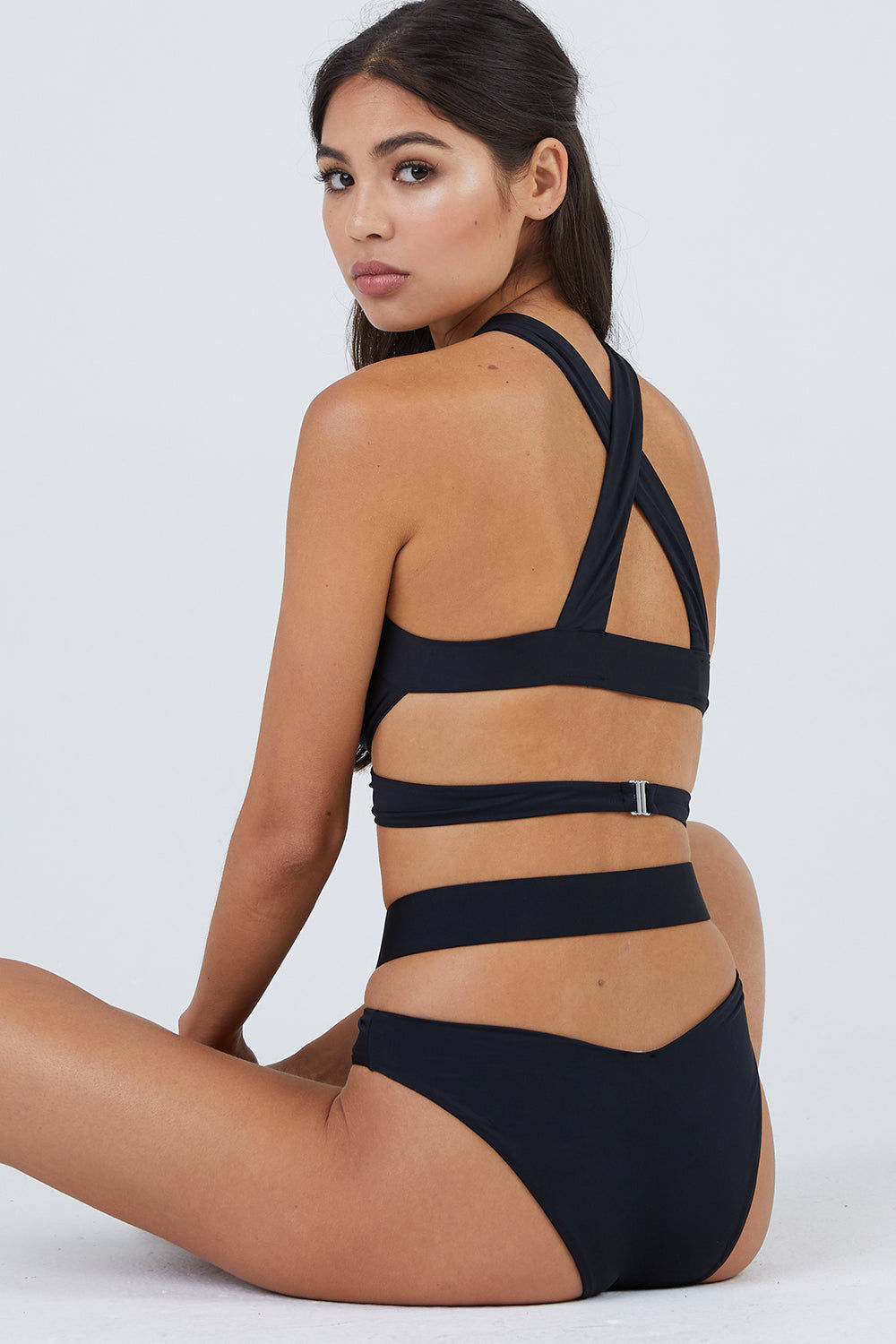 MONICA HANSEN BEACHWEAR Endless Summer Wrap Around Bikini Bottom - Black Bikini Bottom | Black| Monica Hansen Beachwear Endless Summer Wrap Around Bikini Bottom - Black. Forms a diamond cut out in front Criss cross straps  High cut leg  Cheeky coverage  Double fabric on the inside instead of lining Italian fabric 85% Nylon 15% Elastane Manufactured in Italy Hand wash cold.  Dry Flat Back View