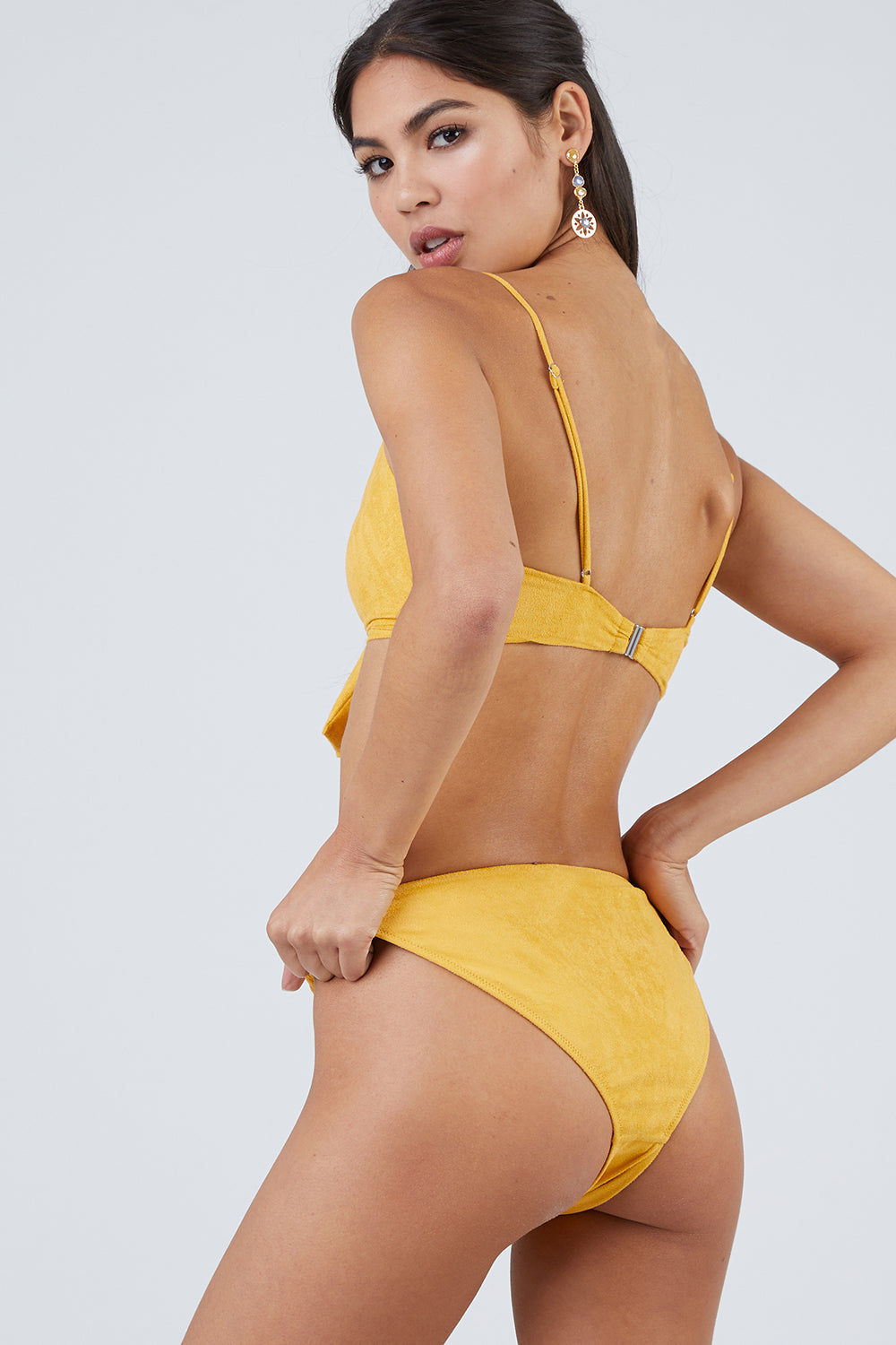 MONICA HANSEN BEACHWEAR Start Me Up Suede Front Scrunch Bikini Bottom - Yellow Bikini Bottom | Yellow| Monica Hansen Start Me Up Suede Front Scrunch Bikini Bottom - Yellow Scrunch detail in front and U shaped back High cut leg Cheeky coverage Double fabric on the inside instead of lining Italian fabric 85% Nylon 15% Elastane Manufactured in Italy Hand wash cold.  Dry flat Back View