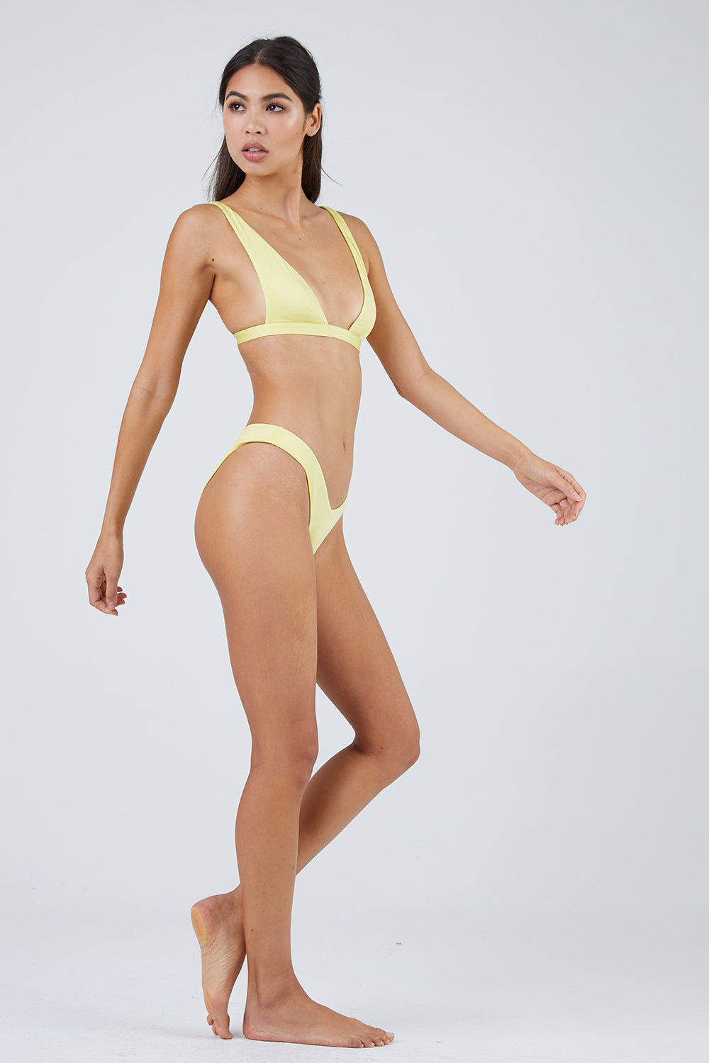 MONICA HANSEN BEACHWEAR Babe Watch Long Triangle Bikini Top - Yellow Bikini Top | Yellow| Monica Hansen Beachwear Babe Watch Long Triangle Bikini Top - Yellow Plunging U-neckline Long triangle top Small nickel colored metal clasp in back Double fabric on the inside instead of lining Italian fabric 85% Nylon 15% Elastane Manufactured in Italy Hand wash cold. Side View