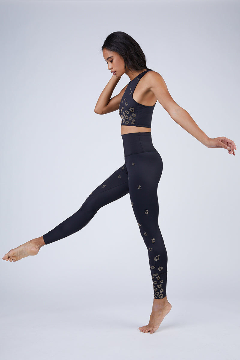 BEACH RIOT Leo High Neck Sports Bra Top - Black Top   Black  Beach Riot Leo High Neck Sports Bra Top - Black. Features:   High neck sports bra  Gold leopard print beads fading from bottom to top Full coverage front  Thick straps  Polyester/Spandex Blend Hand wash cold; lay flat to dry Made in the USA Close View