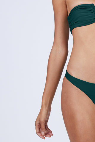 MIKOH Lahaina Low Rise Bikini Bottom - Kelp Bikini Bottom | Kelp| Mikoh Lahaina Low Rise Bikini Bottom - Kelp. Features: Low-rise brazilian cut bikini bottom in luxe solid blue-green fabric. Low rise cut and minimal coverage minimize tan lines and hug your curves without digging into your skin. View: On model, up close front view.