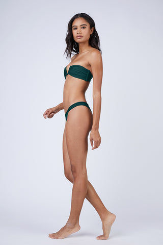 MIKOH Lahaina Low Rise Bikini Bottom - Kelp Bikini Bottom | Kelp| Mikoh Lahaina Low Rise Bikini Bottom - Kelp. Features: Low-rise brazilian cut bikini bottom in luxe solid blue-green fabric. Low rise cut and minimal coverage minimize tan lines and hug your curves without digging into your skin. View: On model,  full side view.