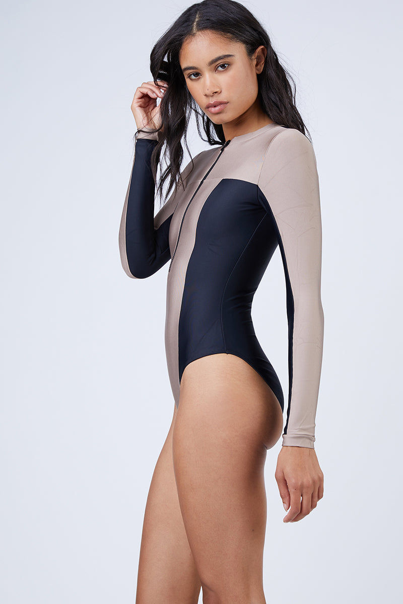 PILYQ Ace Zip Rashguard Bodysuit - Cadillac Nude/Black One Piece | Cadillac Nude/Black| Pilyq Ace Zip Rashguard Bodysuit - Cadillac Nude/Black Long Sleeve Rashguard Bodysuit  V Neckline  Zip Up Front Detail  High Cut Leg Full Coverage Colorblocking of Nude and Black Side View