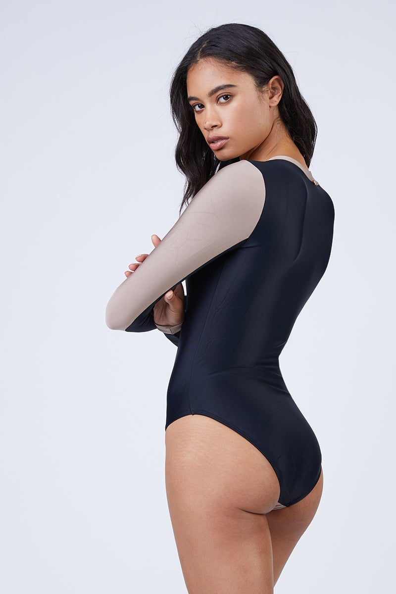 PILYQ Ace Zip Rashguard Bodysuit - Cadillac Nude/Black One Piece | Cadillac Nude/Black| Pilyq Ace Zip Rashguard Bodysuit - Cadillac Nude/Black Long Sleeve Rashguard Bodysuit  V Neckline  Zip Up Front Detail  High Cut Leg Full Coverage Colorblocking of Nude and Black Back View