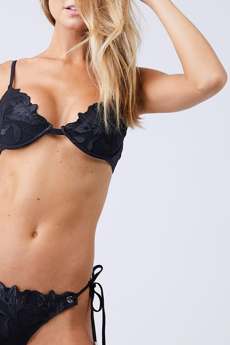 FLEUR DU MAL Lily Side Tie Bikini Bottom - Black Bikini Bottom | Black| Fleur Du Mal Lily Side Tie Bikini Bottom Low-rise cheeky black bikini bottom with delicate embroidered floral detail. Silver grommet hardware offers a modern, stylish take on the classic adjustable side ties. Seamed ruching at cheeky Close View