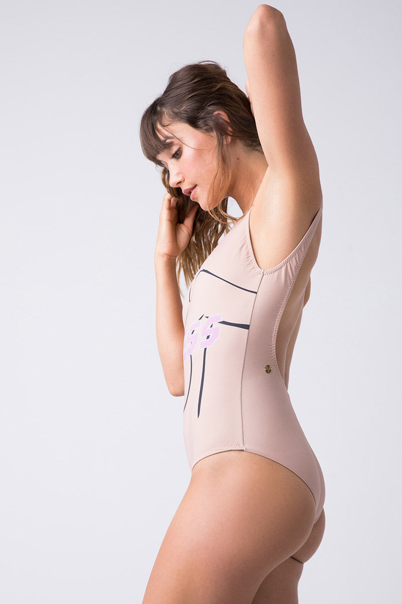 "TRIYA U Neckline One Piece - Topless One Piece | Topless| Triya U Neckline One Piece - Topless Side View U Neckline  Beige One Piece  ""TOPLESS"" in Pink Font  Female Outline on the Front  Low Scoop Back  High Cut Leg Full Coverage  90% Polyamide, 10% Elastane Produced in Brazil Hand wash, cold and dry"