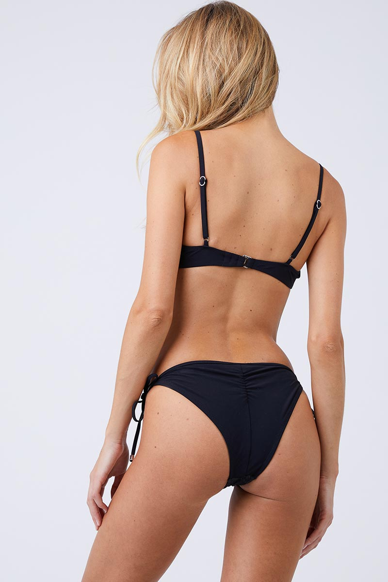 FLEUR DU MAL Lily Side Tie Bikini Bottom - Black Bikini Bottom | Black| Fleur Du Mal Lily Side Tie Bikini Bottom Low-rise cheeky black bikini bottom with delicate embroidered floral detail. Silver grommet hardware offers a modern, stylish take on the classic adjustable side ties. Seamed ruching at cheeky Back View