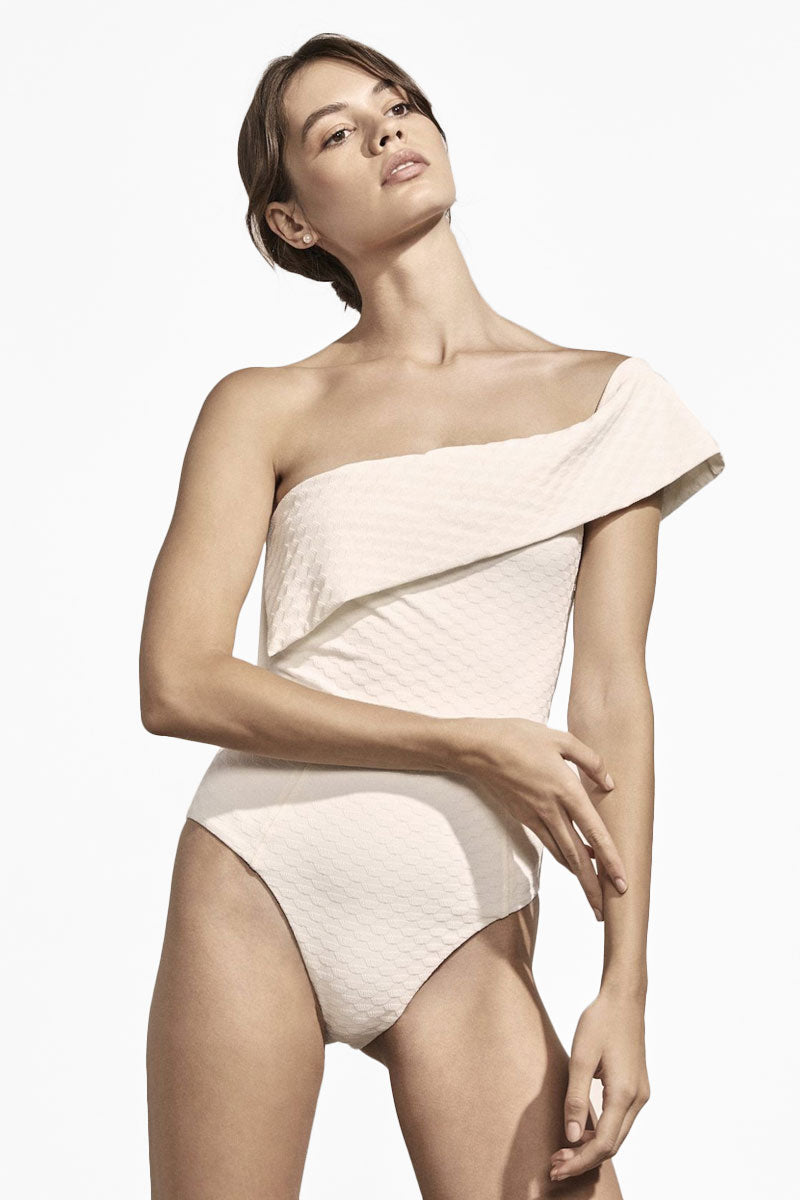 AMAIO SWIM Jeanne One Shoulder Textured One Piece Swimsuit - Ivory One Piece | Ivory| Amaio Swim Jeanne One Shoulder Textured One Piece Swimsuit - Ivory. Features:  One shoulder one piece swimsuit Cheeky-moderate coverage Mid cut legs Geometric Jacquard textured ivory fabric Front View