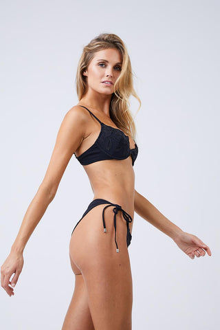 FLEUR DU MAL Lily Side Tie Bikini Bottom - Black Bikini Bottom | Black| Fleur Du Mal Lily Side Tie Bikini Bottom Low-rise cheeky black bikini bottom with delicate embroidered floral detail. Silver grommet hardware offers a modern, stylish take on the classic adjustable side ties. Seamed ruching at cheeky Side View
