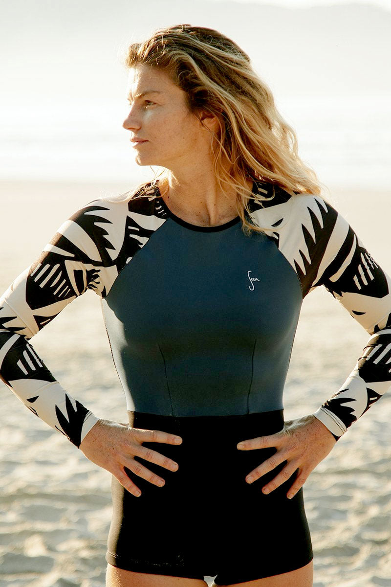 SEEA Dara Color Block Long Sleeve Rashguard Bodysuit - Buzios Abstract Print/ Sea Blue/ Black One Piece | Buzios Abstract Print/ Sea Blue/ Black| Seea Dara Color Block Long Sleeve Rashguard Bodysuit - Buzios Abstract Print/ Sea Blue/ Black Features: Recycled Spandex/ Nylon sleeves and C-Skin fabric body. Fabric rated UPF 30+ - UPF 50+ Original Buzios print. High neck for extra coverage and keyhole tie in the back. Long sleeves and covered back for sun protection. Raglan sleeves for paddling flexibility. Retro cut shorts for extra coverage and secure fit. Made in sunny California. Front View