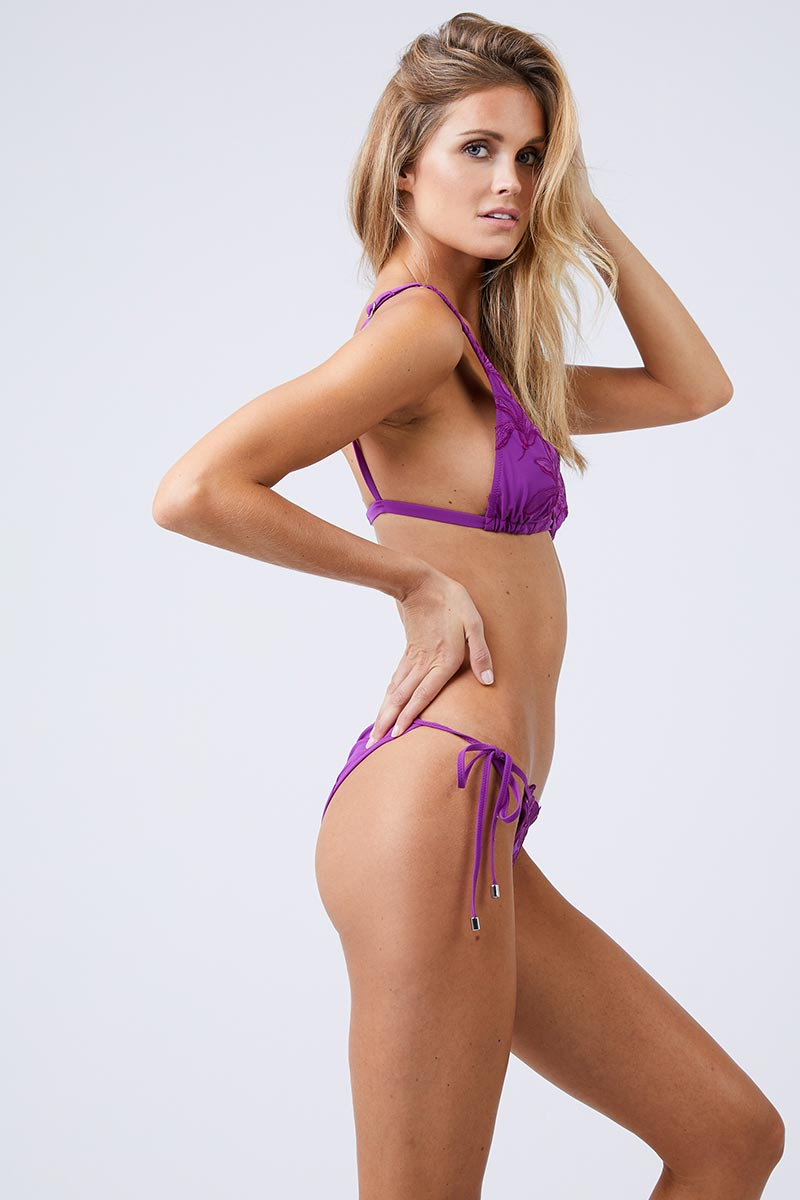 FLEUR DU MAL Lily Side Tie Bikini Bottom - Dragon Fruit Bikini Bottom | Dragon Fruit| Fleur Du Mal Lily Side Tie Bikini Bottom Low-rise bright purple cheeky bikini bottom with delicate embroidered floral detail. Silver grommet hardware offers a modern, stylish take on the classic adjustable side ties. Seamed ruching at cheeky  Side View
