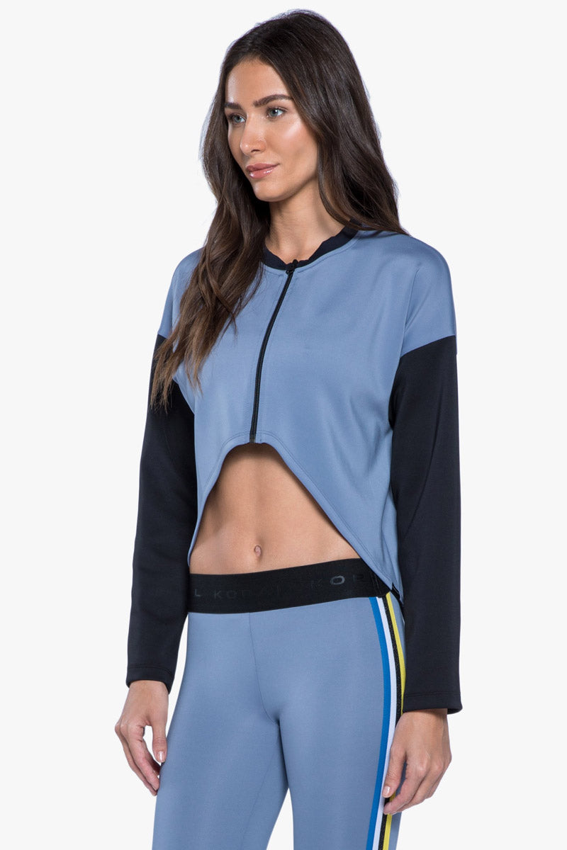 KORAL Ace Jacket - Nova Blue Jacket | Nova Blue| KORAL Ace Jacket.Nova Blue.Features:  Color blocked, front cropped jacket with black trim Meant for Athleisure performance  Fabric: Scuba 86% Polyester, 14% Spandex Machine wash cold, inside out with like colors; No bleach; Tumble dry low MADE IN USA Front View
