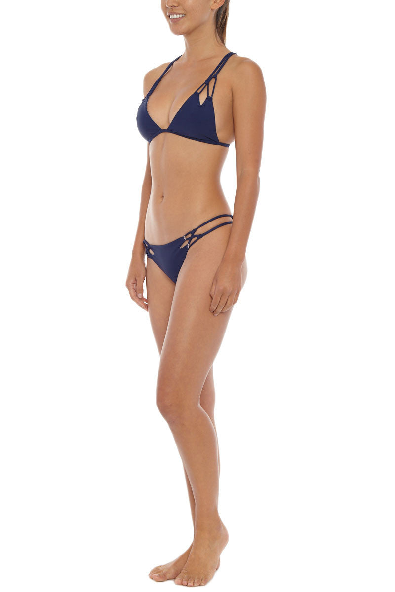 ACACIA Molokini Strappy Low Rise Bikini Bottom - Ocean Navy Bikini Bottom | Ocean| Acacia Molokini Strappy Low Rise Bikini Bottom - Ocean Navy. Features: Low rise, strappy sides, cut-out detail in front and back. Cheeky coverage, stretch fit. View:  On model, full side view.