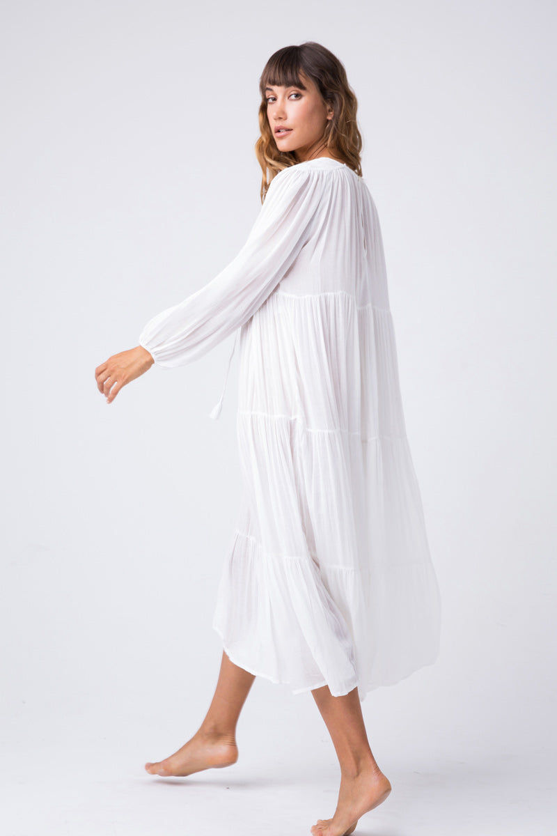 INDAH Belladona Long Sleeve Dress - White Dress | White| Indah Belladonna Long Sleeve Dress - White  Low V neckline with adjustable ties and tassel detail Button closure at the back Wide long sleeves Gathered wrists Three tier construction Hemline about four inches below knee Side Vi