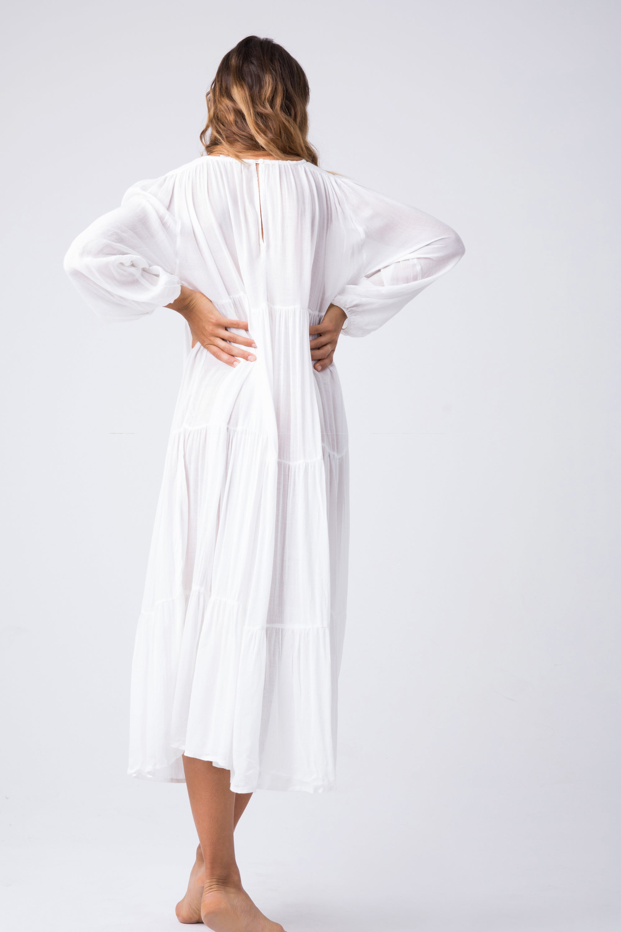 INDAH Belladona Long Sleeve Dress - White Dress | White| Indah Belladonna Long Sleeve Dress - White  Low V neckline with adjustable ties and tassel detail Button closure at the back Wide long sleeves Gathered wrists Three tier construction Hemline about four inches below knee Back Vi