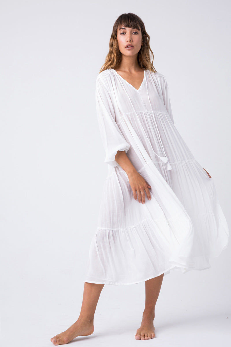 INDAH Belladona Long Sleeve Dress - White Dress | White| Indah Belladonna Long Sleeve Dress - White  Low V neckline with adjustable ties and tassel detail Button closure at the back Wide long sleeves Gathered wrists Three tier construction Hemline about four inches below knee Front View