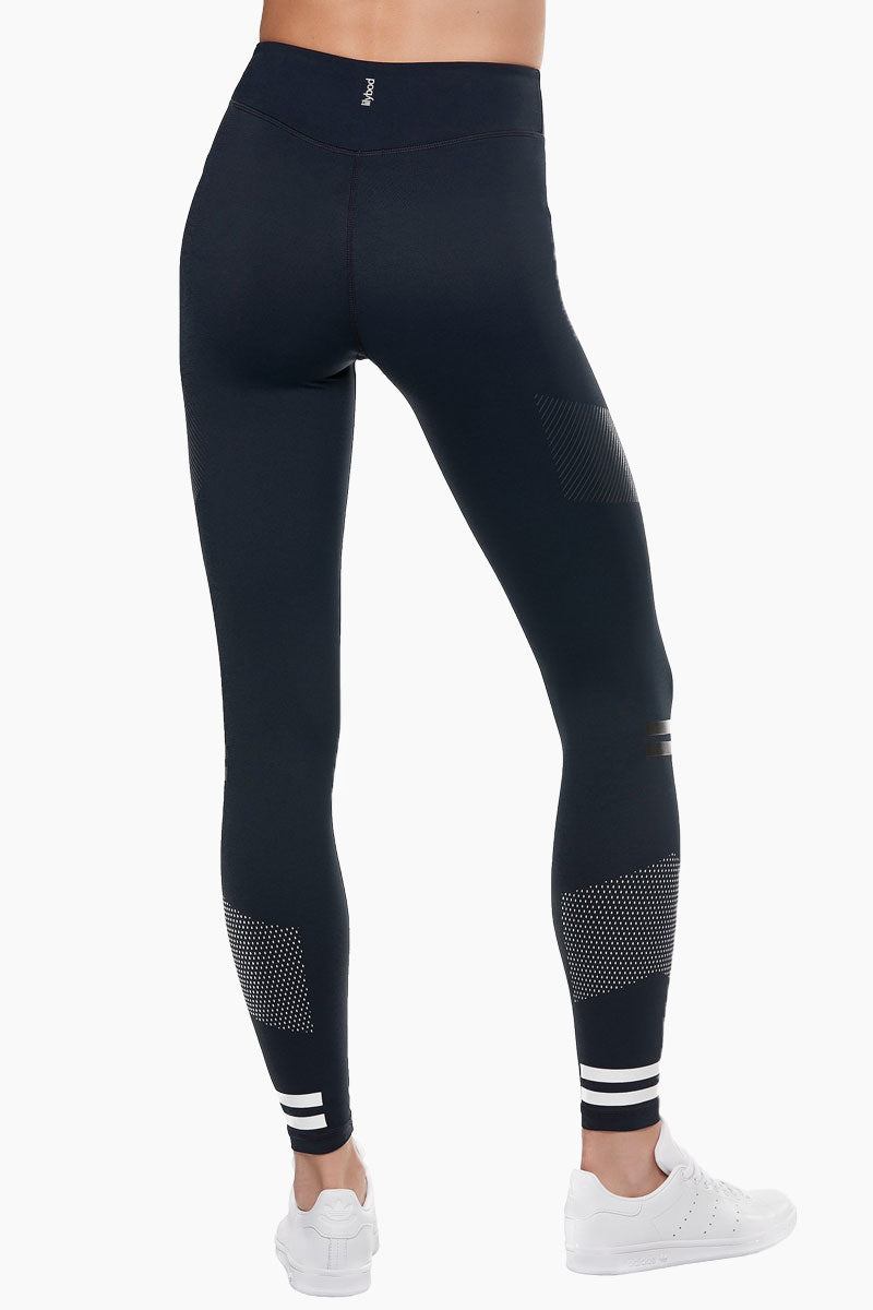LILYBOD Bristol Leggings - Blue Graphite Activewear | Blue Grapl| Lilybod FEATURES: Ankle length legging. Mid rise.  Premium four-way stretch soft touch fabric. Rubber stripe detail. Self color silicon high sheen detail.  Slimming silhouette. Moisture wicking and anti-pilling. Quick dry fabric. High elasticity for perfect shape retention. Shrink & fade resistant. 73% Polyester 27% Spandex. View:  Back View