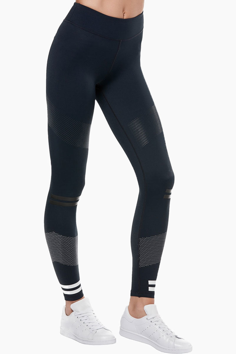 LILYBOD Bristol Leggings - Blue Graphite Activewear | Blue Graphite| Lilybod FEATURES: Ankle length legging. Mid rise.  Premium four-way stretch soft touch fabric. Rubber stripe detail. Self color silicon high sheen detail.  Slimming silhouette. Moisture wicking and anti-pilling. Quick dry fabric. High elasticity for perfect shape retention. Shrink & fade resistant. 73% Polyester 27% Spandex. View:  Front Side View