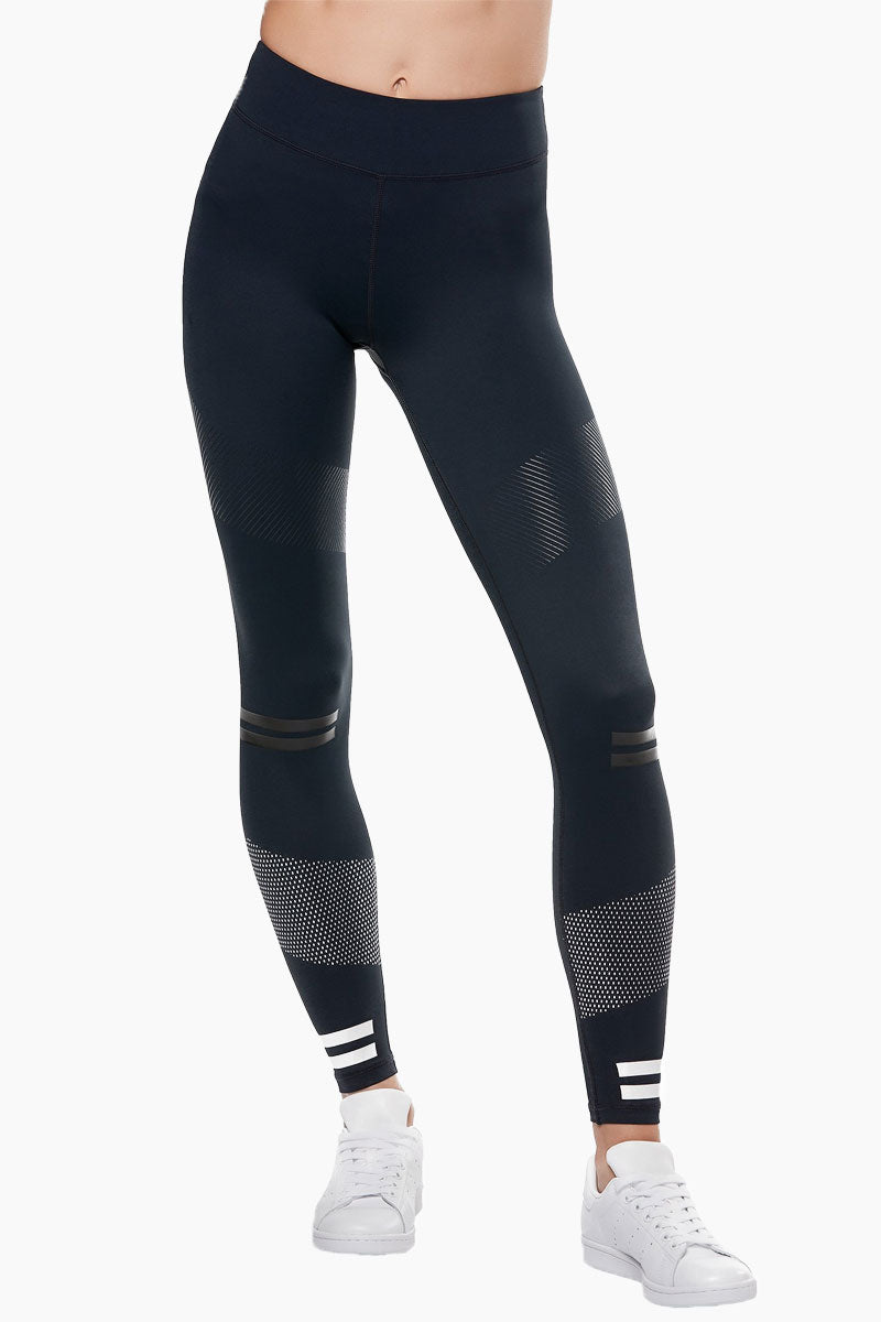 LILYBOD Bristol Leggings - Blue Graphite Activewear | Blue Graphite| Lilybod FEATURES: Ankle length legging. Mid rise.  Premium four-way stretch soft touch fabric. Rubber stripe detail. Self color silicon high sheen detail.  Slimming silhouette. Moisture wicking and anti-pilling. Quick dry fabric. High elasticity for perfect shape retention. Shrink & fade resistant. 73% Polyester 27% Spandex. View: Front View