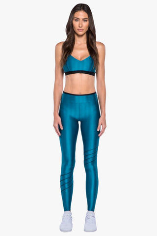 KORAL Cable Sports Bra - Calypso Activewear | Calypso| Koral Cable Sports Bra - Calypso. Features:   Sports bra with piping detail and logo elastic.  Meant for High performance. Slight V Neckline Moderate Coverage Thick Bra Band Racerback  Removable Padding  Made in USA Front View