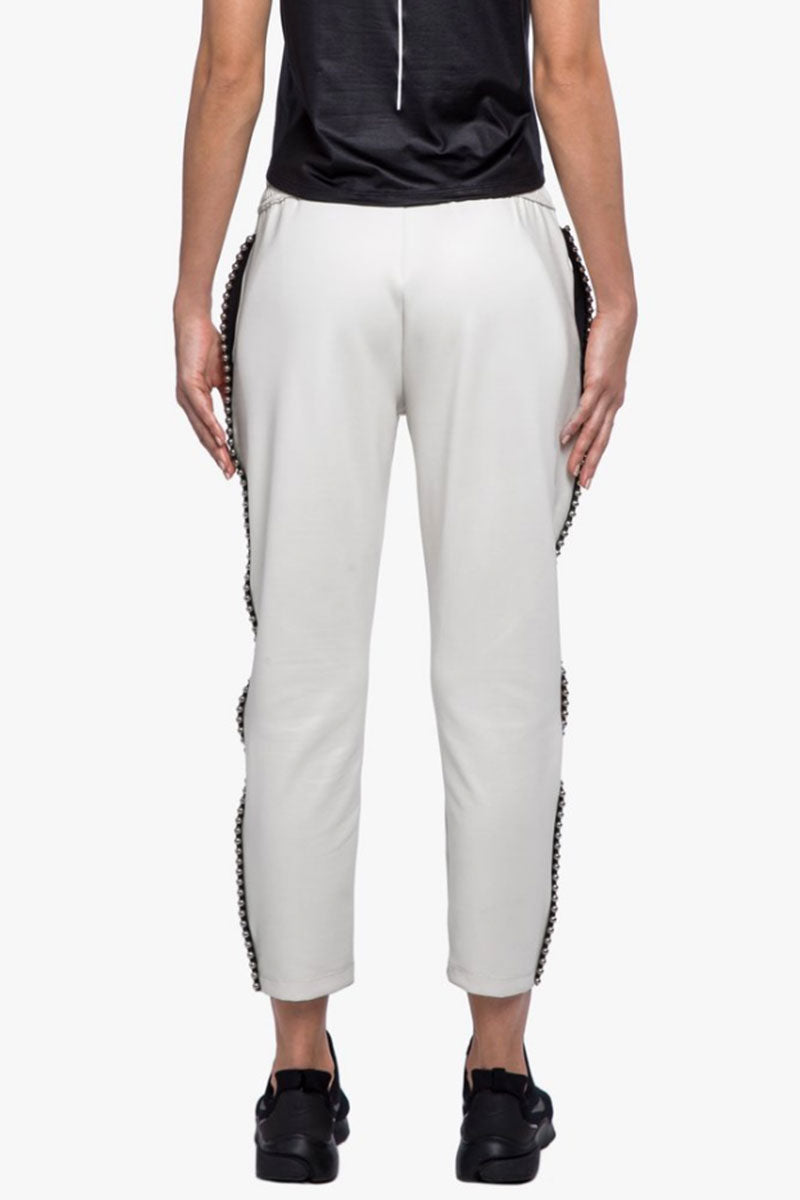 KORAL Chad Scuba Pants - Egret White Pants | Egret White| Koral Chad Scuba Pants - Egret White. Features:  Relaxed fit Cropped above the ankle Drawstring elastic waistband Metallic bead trim detail outseams Fabric: Scuba - 86% Polyester, 14% Spandex Made in the U.S. Back View