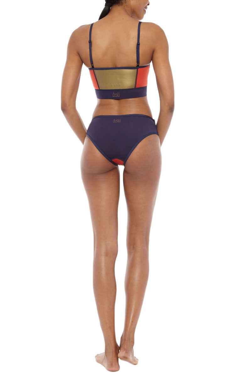 DUSKII Zip Me Up Color Block Full Bikini Bottom - Indigo Purple/Tangelo Red Bikini Bottom    Indigo Purple/Tangelo Red  Duskii Zip Me Up Color Block Zipper Full Bikini Bottom - Indigo Purple/Tangelo Red Low waisted bikini bottoms elongate your torso and side zips can be worn open to reveal inner accent fabric. Moderate backside coverage prevents this suit from riding up no matter how active you get. Back View