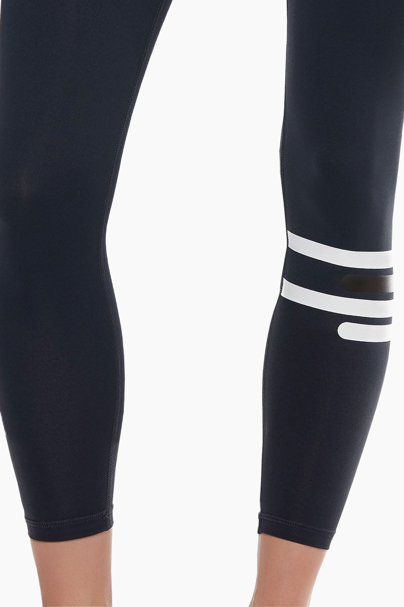 LILYBOD Fleur Leggings - Midnight Zero Activewear | Midnight Zero| Lilybod FEATURES:   Full length legging. Contrast striping on lower left leg. Hipster fit. Premium four-way stretch soft touch fabric. Moisture wicking and anti-pilling. Quick dry fabric. High elasticity for perfect shape retention. Reinforced cover-stitch to sit flat and contoured. Shrink & fade resistant. 73% Polyester 27% Spandex. If you are between sizes we recommend trying a smaller size. View: Detail View