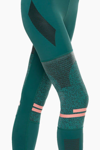 LILYBOD Frankie Leggings - Deep Green Activewear | Deep Green| Lilybod Frankie Leggings - Deep Green. FEATURES:   73% poly , 27% spandex Elasticized waistband Engineered knee panels with unique textured fabric Screen print graphics throughout Pink silicon stripe detail Sheer mesh side panels. View:  Side View