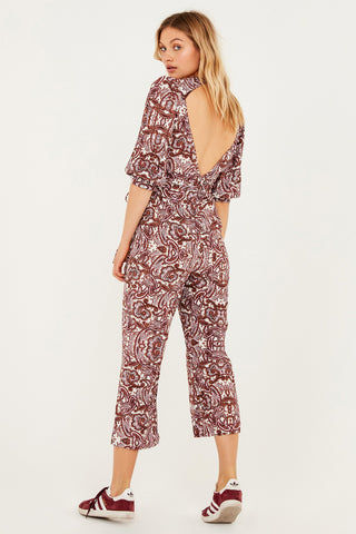 FOR LOVE AND LEMONS Georgi Plunging Cropped Jumpsuit - Lilac Paisley Print Jumpsuit | Lilac Paisley Print| For Love And Lemons Georgi Plunging Cropped Jumpsuit - Lilac Paisley Print Plunging v-neck cropped jumpsuit in muted rose paisley print. Adjustable drawstring cuffs and fixed waist sash allow you to customize a flattering fit with a pretty feminine bow. Crepey rayon/viscose fabric is cut in a slim fit that drapes perfectly over your curves. Cropped legs with slight flare add a playfully laidback finishing touch. Back View