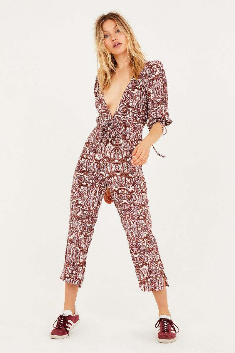 FOR LOVE AND LEMONS Georgi Plunging Cropped Jumpsuit - Lilac Paisley Print Jumpsuit | Lilac Paisley Print| For Love And Lemons Georgi Plunging Cropped Jumpsuit - Lilac Paisley Print Plunging v-neck cropped jumpsuit in muted rose paisley print. Adjustable drawstring cuffs and fixed waist sash allow you to customize a flattering fit with a pretty feminine bow. Crepey rayon/viscose fabric is cut in a slim fit that drapes perfectly over your curves. Cropped legs with slight flare add a playfully laidback finishing touch. Front View