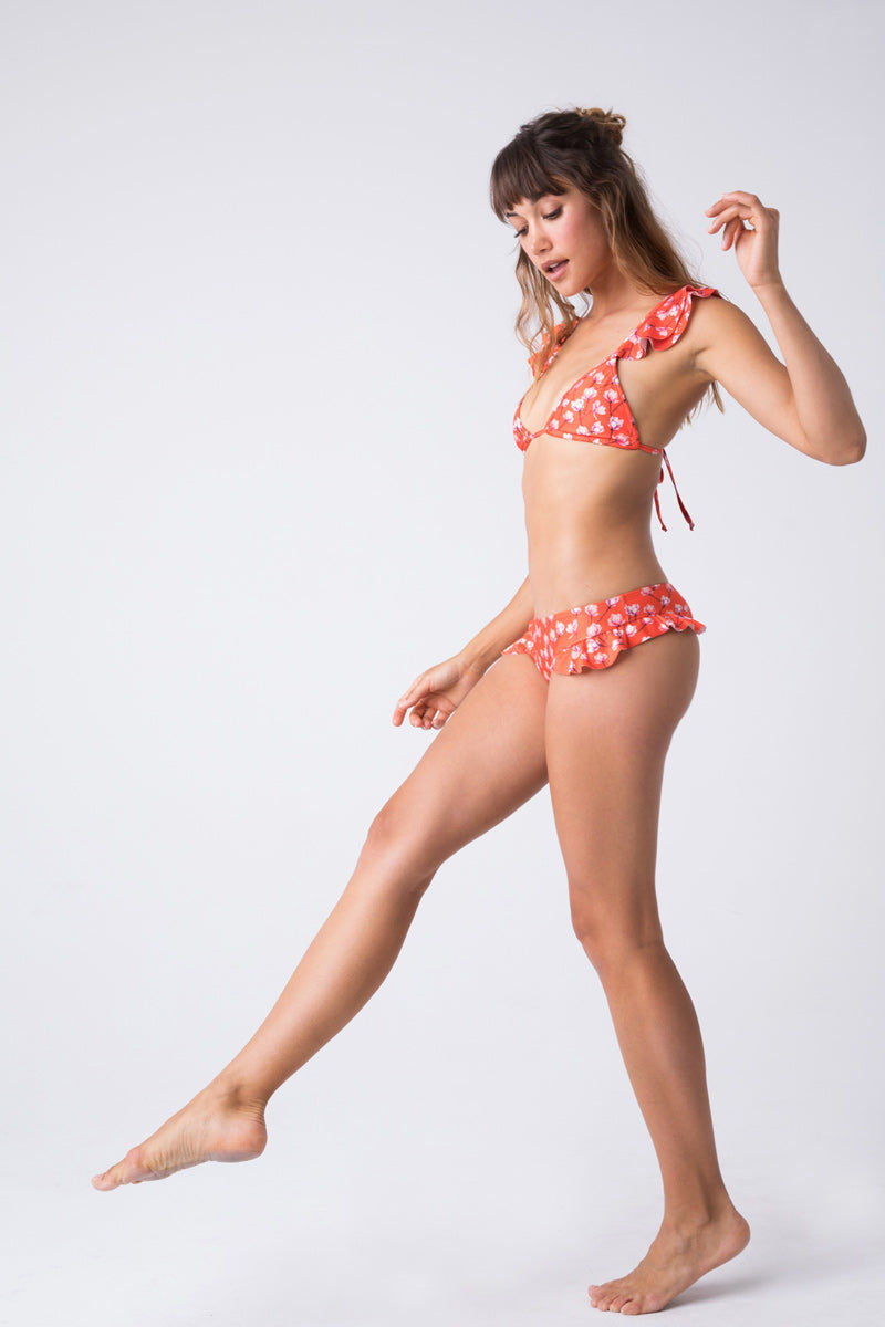 VERDELIMON Holguin Top - Red Blossom Bikini Top | Red Blossom| Verdelimon Holguin Top - Red Blossom Low v-cut bikini top with adjustable bust coverage. Red-orange fabric offset by a pink cherry blossom print. Ruffle shoulder straps. Criss cross back design. Adjustable straps tie at back.