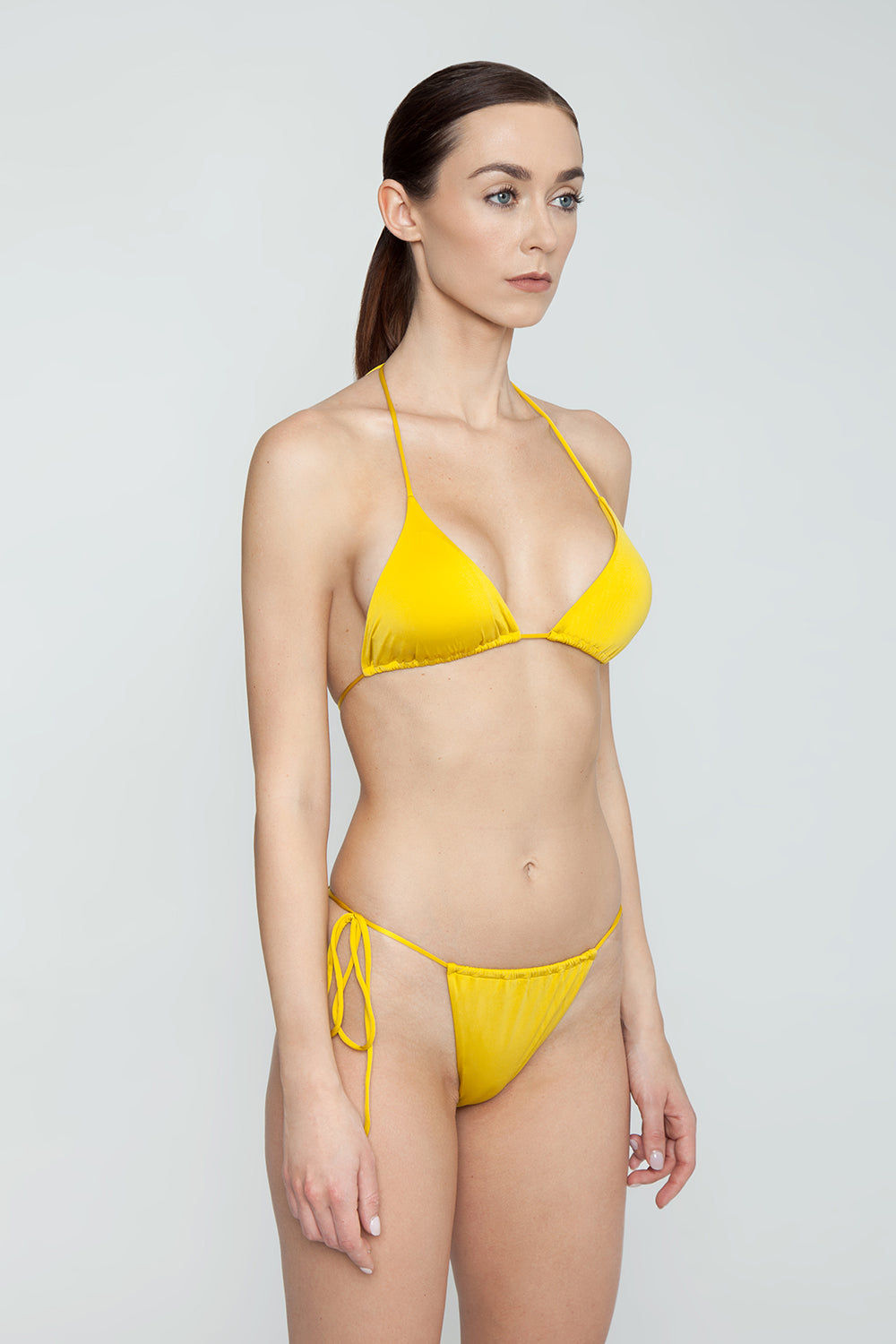 MONICA HANSEN BEACHWEAR That 90's Vibe String Bikini Bottom - Green Olive Bikini Bottom | Green Olive| Monica Hansen That 90's Vibe String Bikini Bottom - Green Olive Single tie side bikini bottom Thin string sides High cut leg  Adjustable coverage in front and back Skimpy to cheeky coverage  Side View