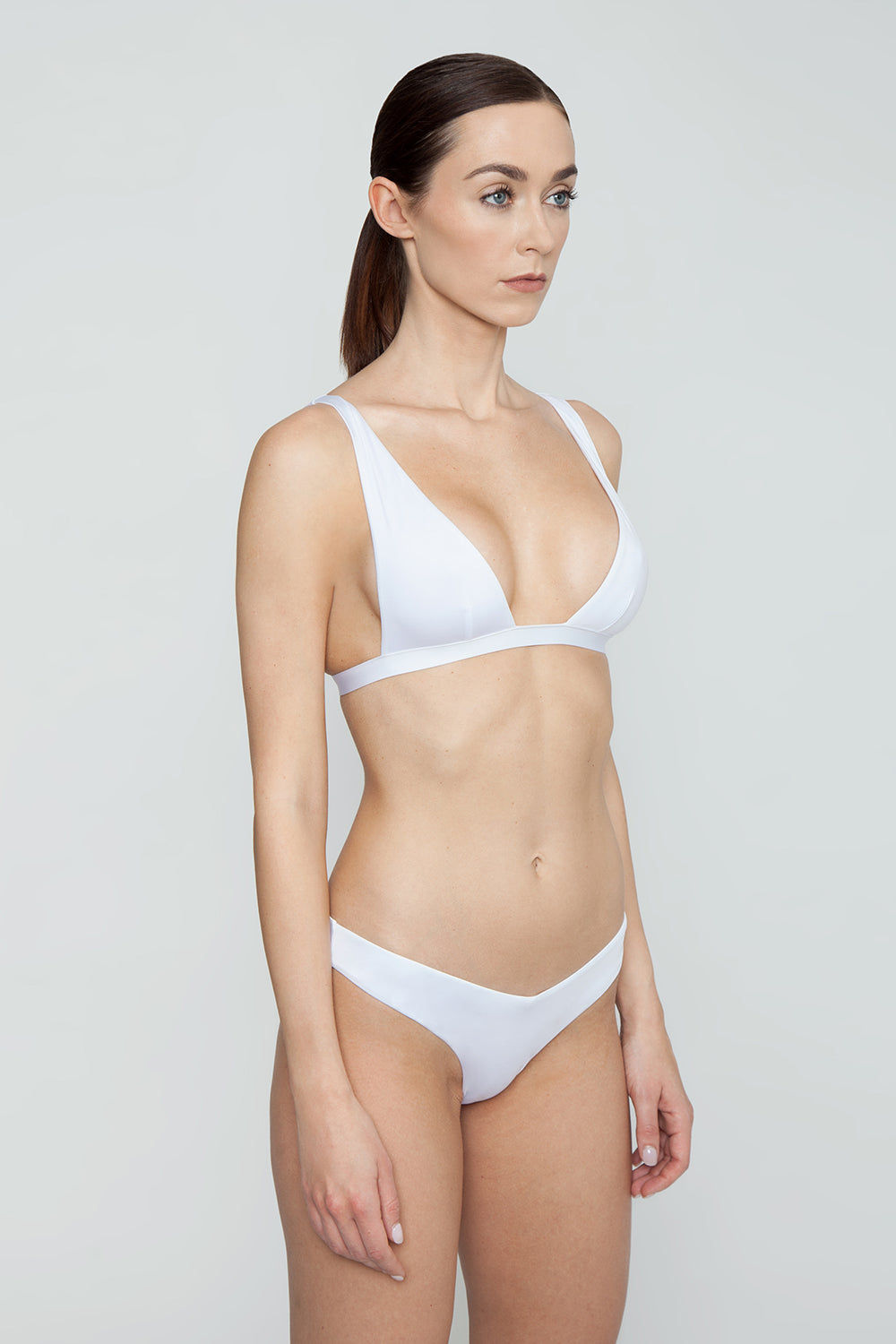 MONICA HANSEN BEACHWEAR Babe Watch Long Triangle Bikini Top - White Bikini Top | White| Monica Hansen Beachwear Babe Watch Long Triangle Bikini Top - White Features:  Plunging U-neckline Long triangle top Small nickel colored metal clasp in back Double fabric on the inside instead of lining Italian fabric 85% Nylon 15% Elastane Manufactured in Italy Hand wash cold.  Dry Flat Side View