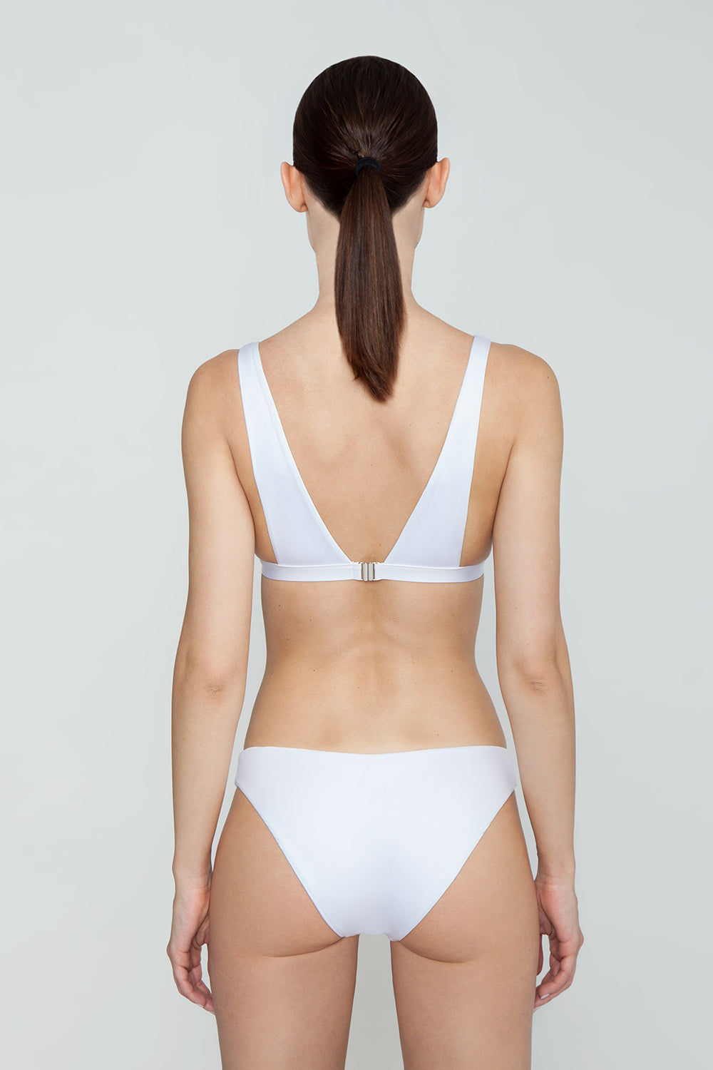 MONICA HANSEN BEACHWEAR Babe Watch Long Triangle Bikini Top - White Bikini Top | White| Monica Hansen Beachwear Babe Watch Long Triangle Bikini Top - White Features:  Plunging U-neckline Long triangle top Small nickel colored metal clasp in back Double fabric on the inside instead of lining Italian fabric 85% Nylon 15% Elastane Manufactured in Italy Hand wash cold.  Dry Flat Back View