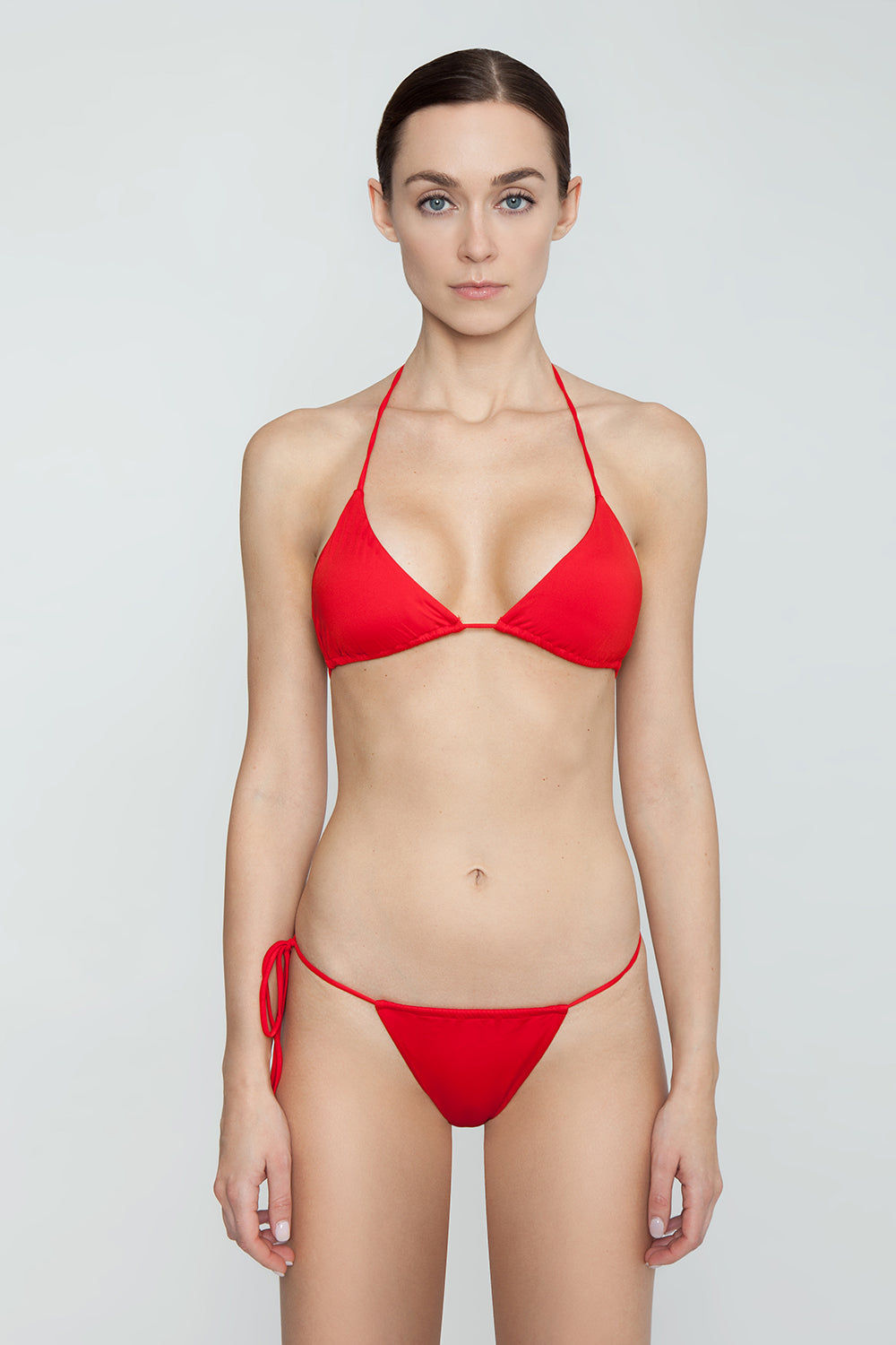 MONICA HANSEN BEACHWEAR That 90's Vibe String Bikini Bottom - Red Bikini Bottom   Red  Monica Hansen That 90's Vibe String Bikini Bottom - Red Single tie side bikini bottom Thin string sides High cut leg  Adjustable coverage in front and back Skimpy to cheeky coverage  Front View