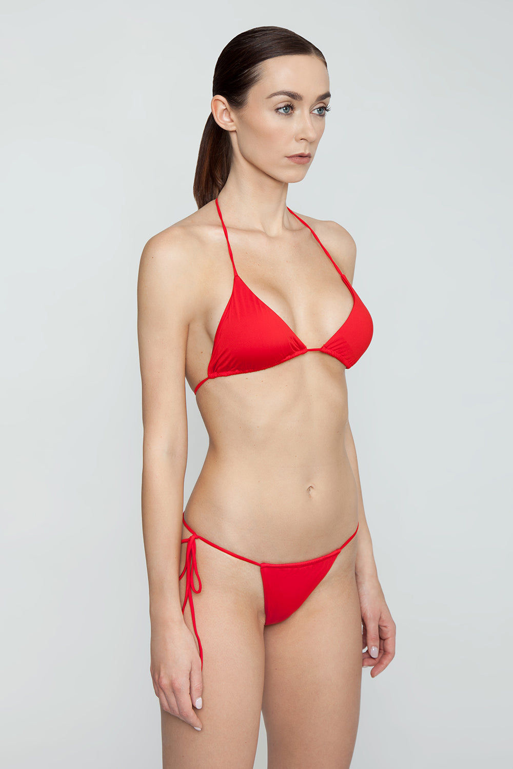 MONICA HANSEN BEACHWEAR That 90's Vibe String Bikini Bottom - Red Bikini Bottom   Red  Monica Hansen That 90's Vibe String Bikini Bottom - Red Single tie side bikini bottom Thin string sides High cut leg  Adjustable coverage in front and back Skimpy to cheeky coverage  Side View