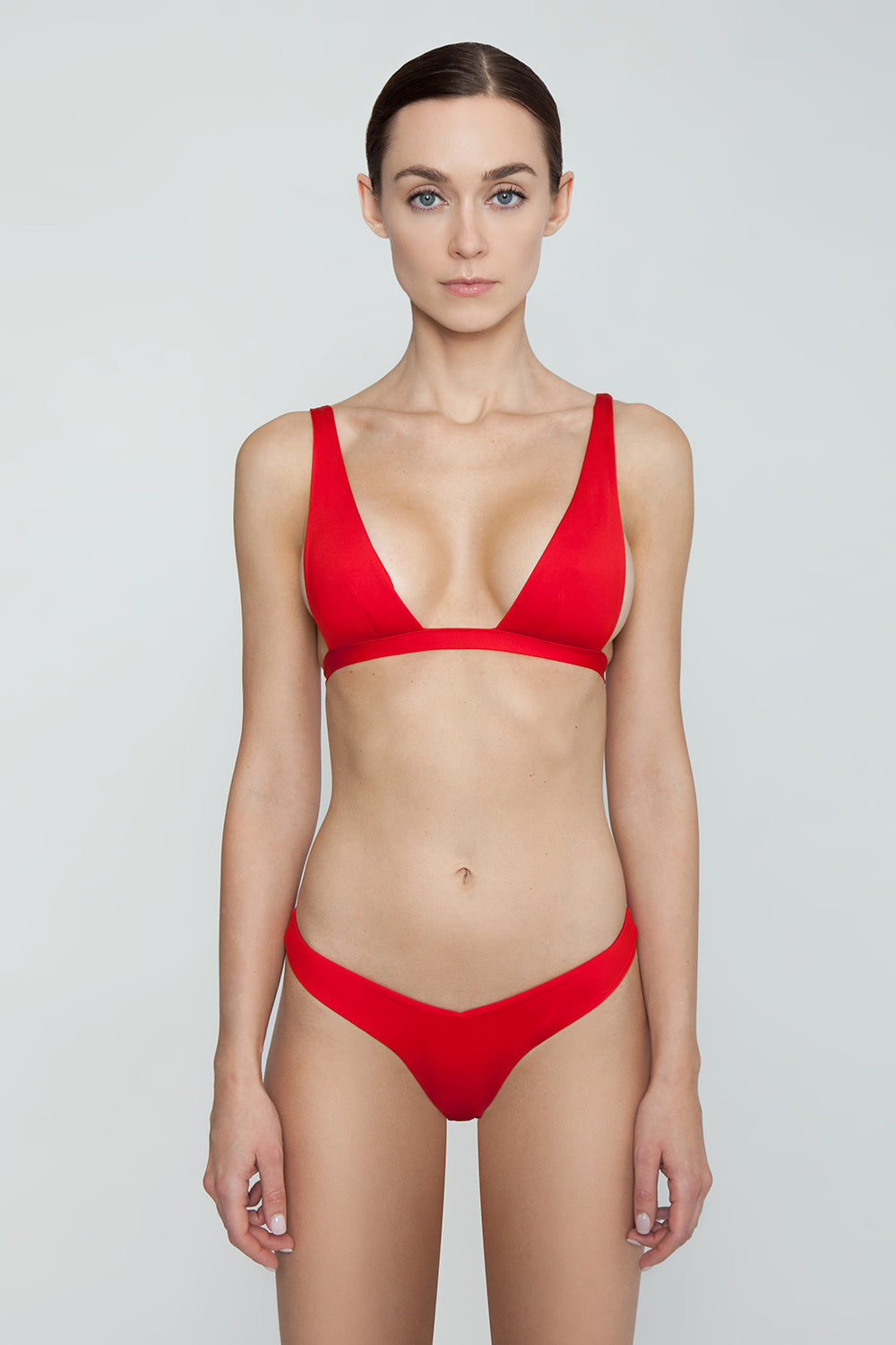 MONICA HANSEN BEACHWEAR Babe Watch V Bikini Bottom - Red Bikini Bottom | Red| Monica Hansen Beachwear Babe Watch V Bikini Bottom - Red Features:  Waist cut down in a V shape in front and in back Sides can be worn low rise or mid rise High cut leg  Cheeky coverage Italian fabric 85% Nylon 15% Elastane Manufactured in Italy Hand wash cold.  Dry Flat Front View